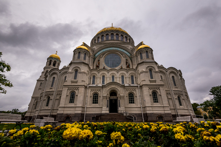 Exterior view of majestic St Nicholas Naval Cathedral with gold cupolas and park in frontal square, Kronstadt. Stock Photo