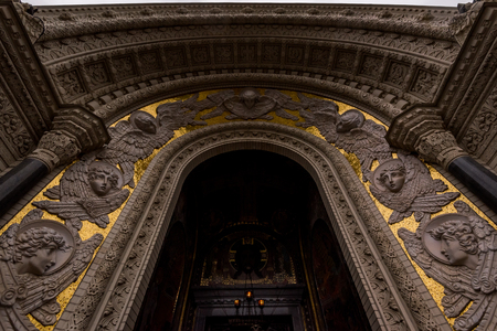 From below shot of entrance arch of St Nicholas Naval Cathedral decorated with plaster work and gold.