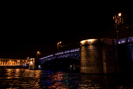 Exterior view of beautiful illuminated bridge crossing channel of Saint Petersburg in night time.