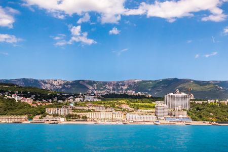 Bâtiments contemporains de la ville de villégiature situés sur la côte de la mer bleue majestueuse près de la montagne par temps nuageux