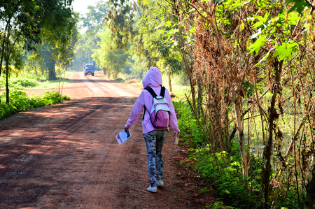 inconvenient: Girl backpacker walking away on dirt road. Stock Photo