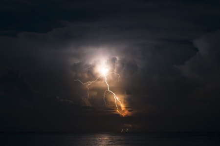 forked: Brilliant forked lightning over the ocean Stock Photo