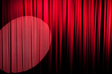 deliberate: A red velvet stage curtain with deliberate vignetting. Stage light included to the left    Part of a series Stock Photo