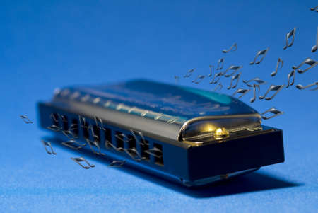harmonica: A photo of a harmonica and notes, on a blue background Stock Photo