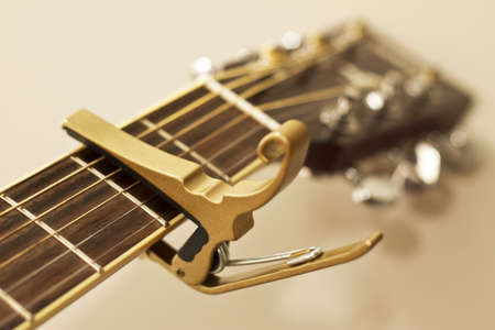 capo: An image of a capo for a stringed istrument.  Shallow depth of field.  Focused on the capo. Stock Photo