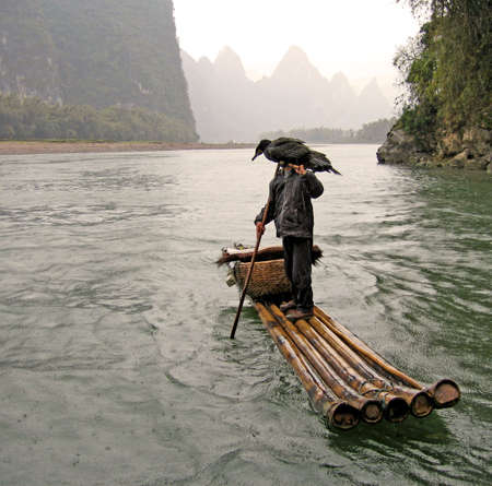 lone fisherman carries his cormorant, used for fishing the Li River Stock Photo