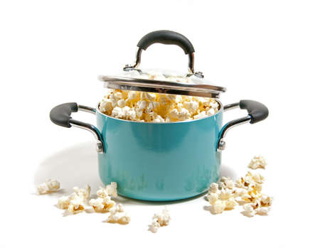 freshly popped corn overflowing in kettle isolated on white