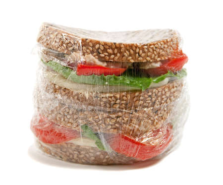 tuna sandwich in plastic wrap isolated on white