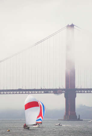 two yachts in full sail pass under the golden gate in fog Archivio Fotografico