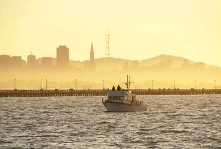 silhouettes of berkeley pier and the koit tower at sunset photo
