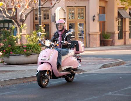 een 60 jaar oude vrouw op haar roze motor