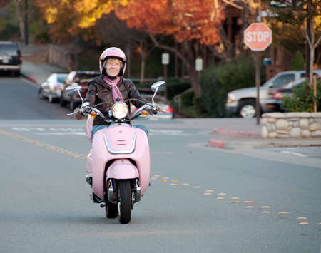 youthful sixty year old woman riding down the street Stock Photo