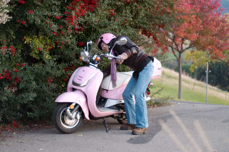 a female motorist parks her scooter next to red berries