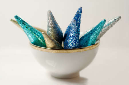 glittery christmas decorations in a gold rimmed bowl