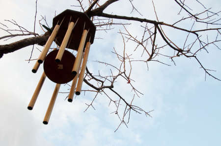 gold wind chimes against a blue sky