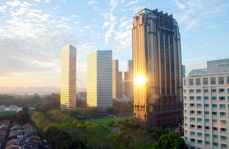 zons opgang in de stad met de singapore flyer op de achtergrond.  Stockfoto