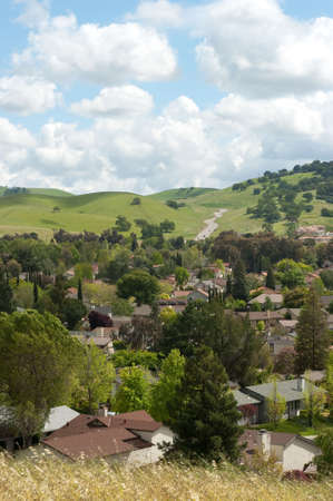 rolling hills and clouds behind a residential community Archivio Fotografico