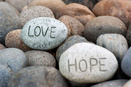love and hope carved into round rocks
