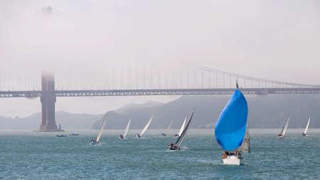 zeilboot met blauwe spinnaker zeil door de golden gate bridge gehuld in mist