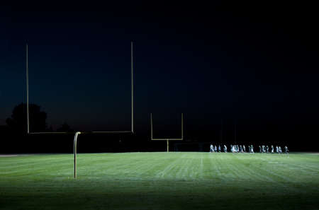football players running on the field at night Stock Photo - 8385422