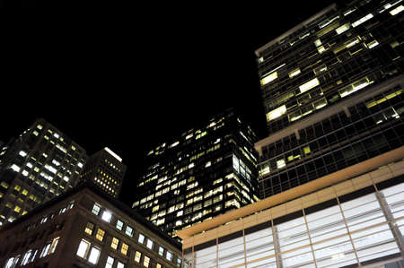 low angle shot of modern buildings lit up at night with copy space