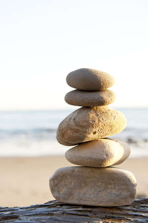 rocks stand in perfect balance on a piece of drftwood Stock Photo
