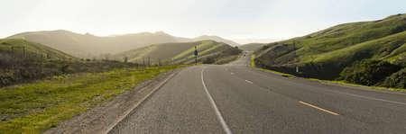 view of center line divider on highway cutting through coastal hills Archivio Fotografico