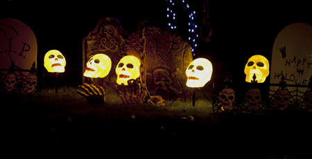 ghoulish: lighted skullcaps in a graveyard