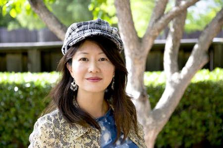 smiling asian woman with herringbone cap