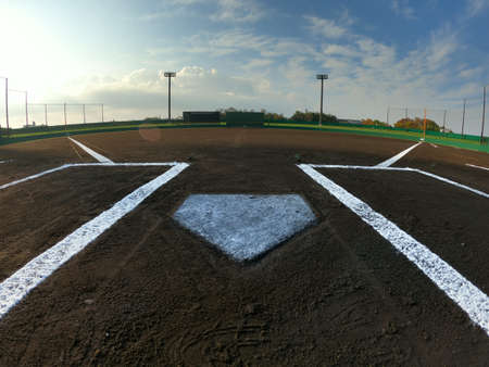 Early in the morning, under a clear sky, the baseball field was clean before the game.