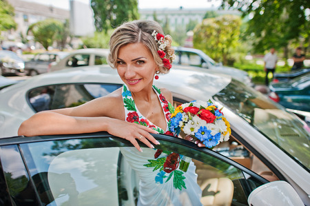 supercar: Blonde bride in traditional dress near exotic supercar