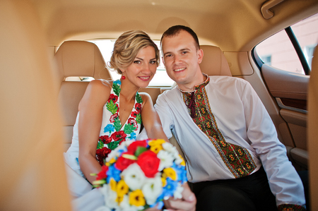 supercar: Wedding beautiful couple in traditional dress in exotic supercar Stock Photo