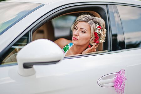 supercar: Wedding beautiful bride in traditional dress in exotic supercar looked at the mirror Stock Photo