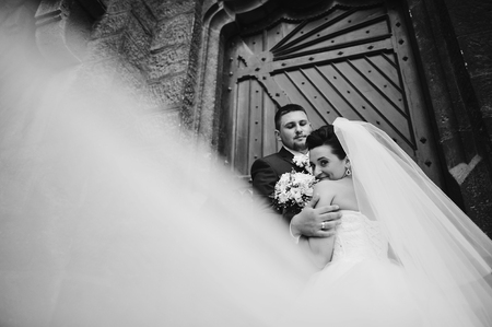 catholic wedding: wedding couple near old catholic church
