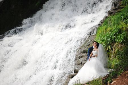 beautiful wedding couple near waterfall photo