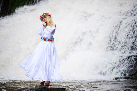 stay beautiful: Young  beautiful blonde girl in traditional dress stay under waterfall