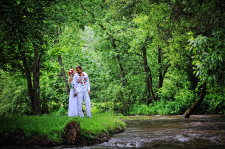 stay beautiful: Young lower beautiful couple in traditional dress stay near the river