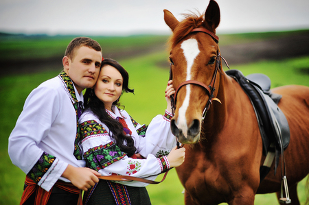 horse love horse kiss animal love: Young couple on national dress with horses