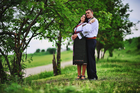 horse love horse kiss animal love: Young couple on national dress embrace on park