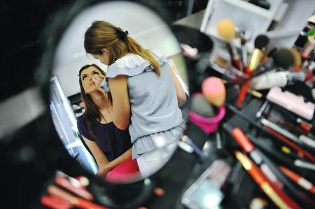 Young brunette bride applying wedding make-up by make-up artist