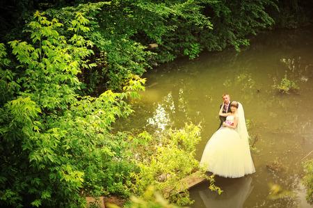 wedding couple standing on the dock lake photo