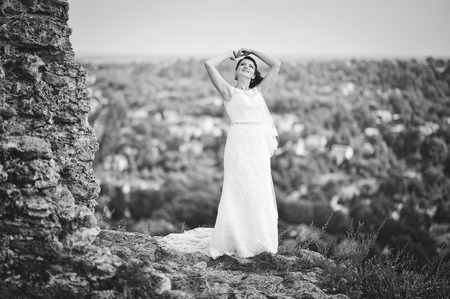 posed: Bride posed over cliff Stock Photo