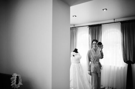 looked: Young brunette bride looked at the mirror