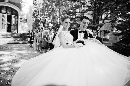 happy wedding: Groom holding bride on hands happy after wedding registration