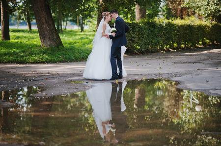 siluet: exciting elegant wedding couple walking at park in love, siluet on water