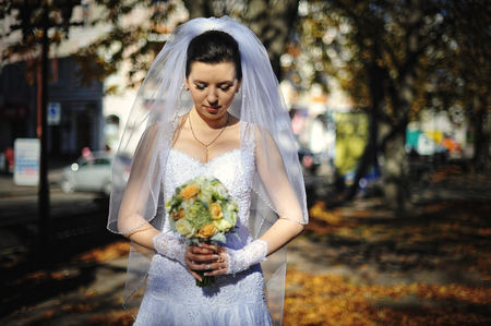 looked: Bride in autumn shadows looked at the wedding bouquet Stock Photo