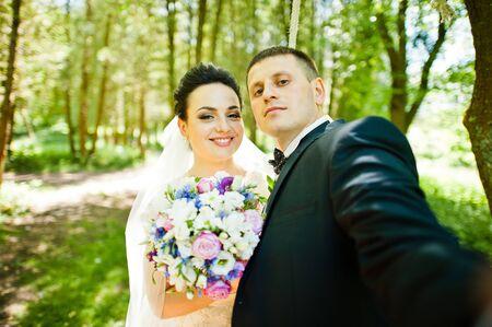 gorgeus: Gorgeus wedding couple on green sunny forest. Groom doing selfie