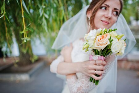 voile: Gentle bride play with veil and bouquet