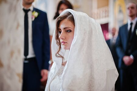 voile: a bride at handkerchief is kneeling in church