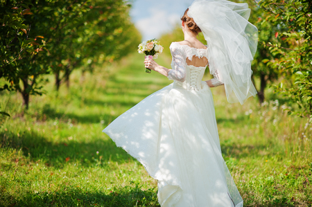 gentle: Gentle bride walking at apple garden